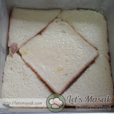 Potong roti supaya muat loyang, celupkan roti dlm susu & susun dalam loyang yg sudah digris.