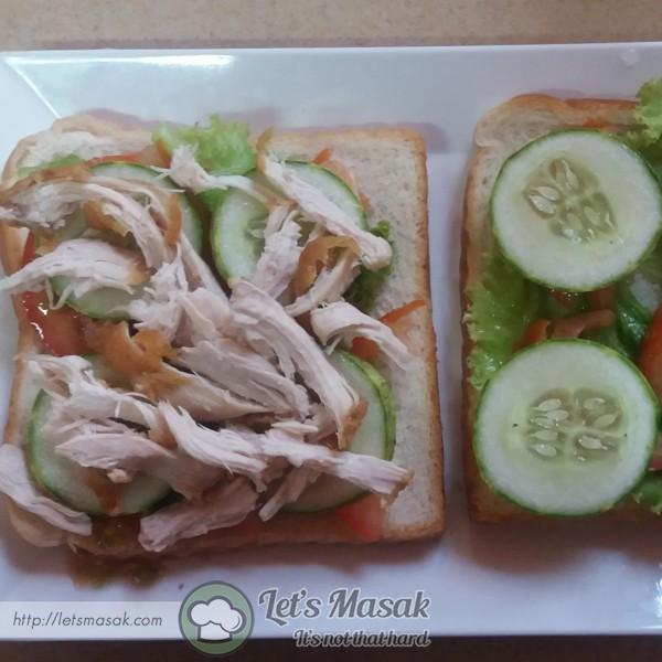 Susunkan daun salad, hirisan tomato & hirisan timun atas roti putih. Taburkan isi ayam yang dicarik.