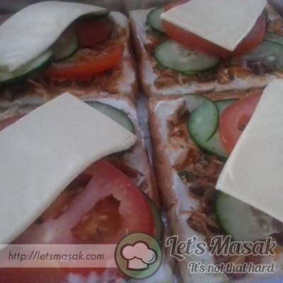 Lapiskan dengan sardin tadi & letak hirisan tomato serta timun. Atas sekali letakkan kepingan keju yang telah dibelah 2.