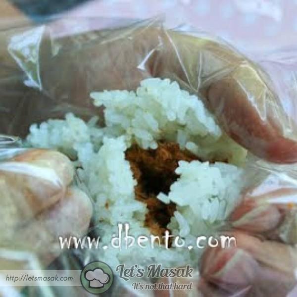 Kepal nasi menjadi bulat. sekali dengan plastik supaya nasi tak melekat pada tangan.