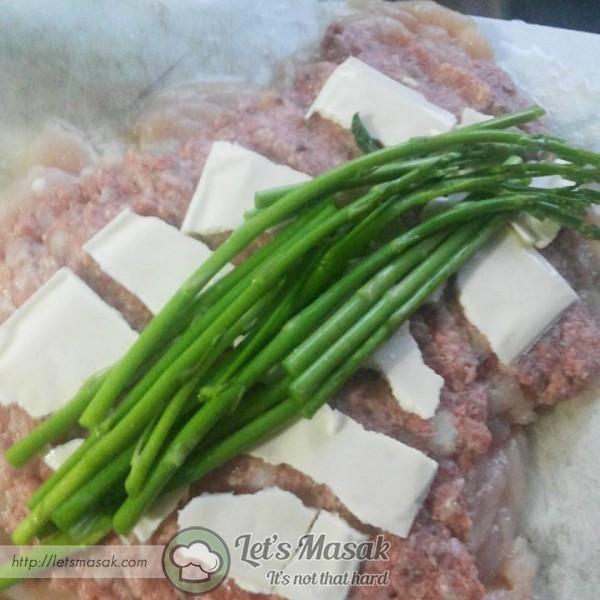 Letak asparagus di tengah. gulungkan ayam kemas dan padat.