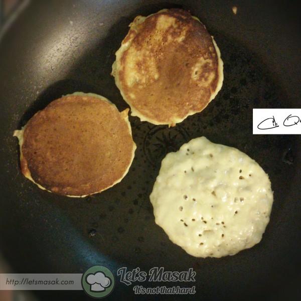 Tunggu sebentar dalam 1-2 minit supaya  pan panas dgn sekata. Terbalikkan penkek bila permukaan atas mula 'berbuih'.